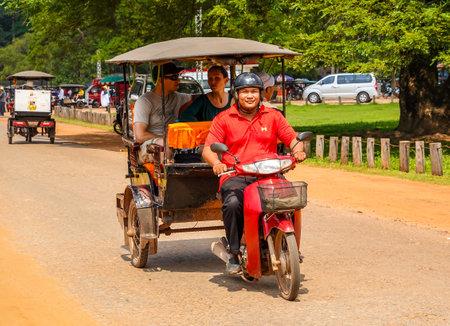 SIEM RIEP, CAMBODIA - NOVEMBER 5, 2019: Tuk Tuk driver bring tourists for Angkor Wat Tours in Cambodia Editöryel