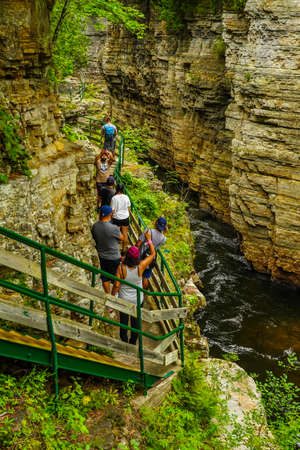 AUSABLE CHASM, NEW YORK - AUGUST 22, 2020: Visitors descending all the way down inside of the chasm trekking riverwalk trailc at Ausable Chasm in Upstate New York.