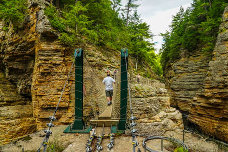 AUSABLE CHASM, NEW YORK - AUGUST 22, 2020: Visitor crossing adventurous rope bridge over Ausable River at Ausable Chasm in Upstate New York. The gorge is about two miles 3.2 km long