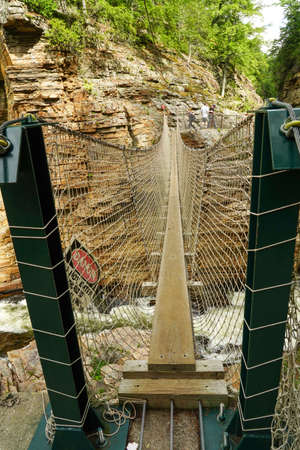 Adventurous rope bridge over Ausable River seen at Ausable Chasm in Upstate New York. The gorge is about two miles 3.2 km long and is a tourist attraction in the Adirondacks region of Upstate New York