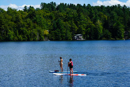LAKE PLACID, NEW YORK - AUGUST 20, 2020: Water boarder enjoys summer day on Mirror Lake in Lake Placid, New York State