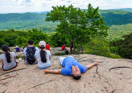 BEAR MOUNTAIN, NEW YORK - JUNE 21, 2020: Hikers enjoy Hudson Valley view at the summit of Bear Mountain. It provides a view of four states and the skyline of Manhattan Sajtókép
