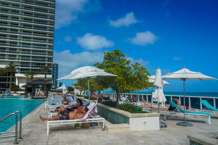 HALLANDALE BEACH, FLORIDA - JANUARY 1, 2021: Guests enjoy outdoors by the luxury condominium pool at Hallandale Beach in South Florida. Hallandale Beach is a city in Broward County, Florida