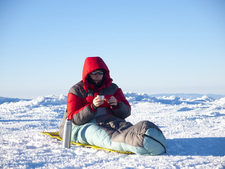 sleeping bag: A man sits in a sleeping bag and drinking tea from a bottle on the background of the winter mountains.