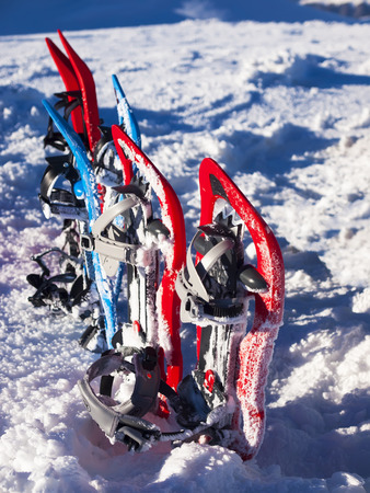 snowshoes: Red and blue snowshoes on snow in the mountains. Stock Photo