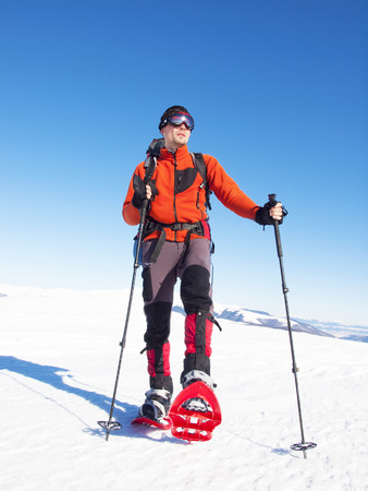 snowshoes: The man in snowshoes and with trekking poles is in the mountains.
