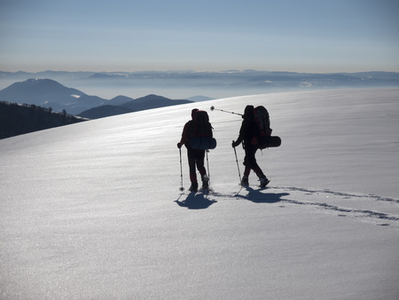 Men in snowshoes and with trekking poles go in the mountains. Archivio Fotografico