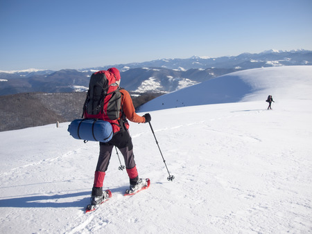 Men in snowshoes and with trekking poles go in the mountains. photo