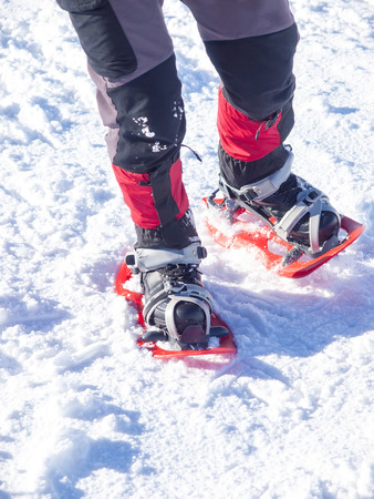 snowshoes: Feet in red snowshoes on snow. Stock Photo