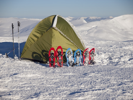 snowshoes: Snowshoes and snow-covered tent on snow in the mountains. Stock Photo