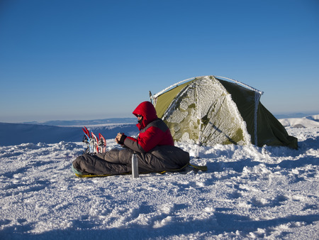 A man sits in a sleeping bag near the tent and snowshoes and drinking tea from a thermos on the background of the winter mountains.