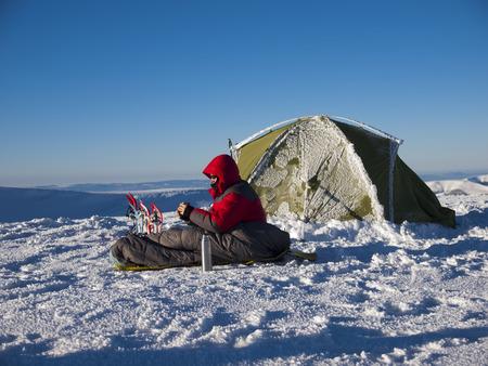 Ein Mann sitzt in einem Schlafsack in der Nähe des Zeltes und Schneeschuhe und trinken Tee aus einer Thermoskanne auf dem Hintergrund der Winter Berge. Standard-Bild - 38603125