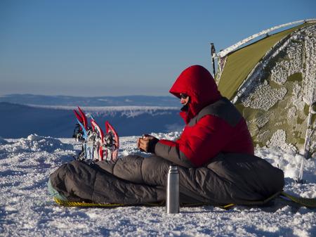 Un hombre se sienta en un saco de dormir cerca de la tienda de campaña y las raquetas de nieve y beber té de un termo en el fondo de las montañas de invierno. Foto de archivo - 38603127