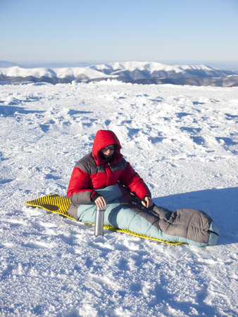 A man sits in a sleeping bag and drinking tea from a thermos on the background of the winter mountains. Archivio Fotografico