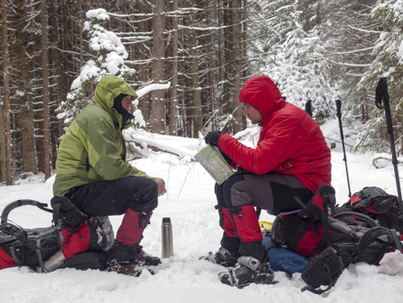 snowshoes: Men in snowshoes sit on backpacks and watch the map in the winter forest.