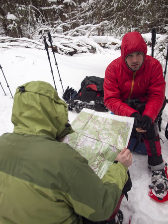 Men in snowshoes sit on backpacks and watch the map in the winter forest. photo