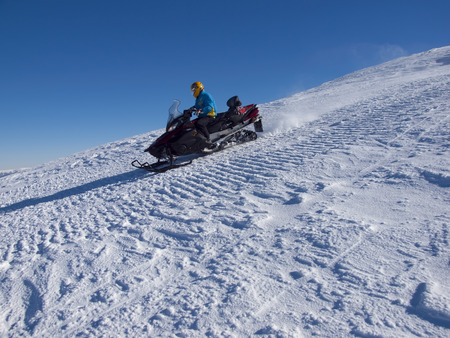 The man riding on the snowmobile from the mountain.