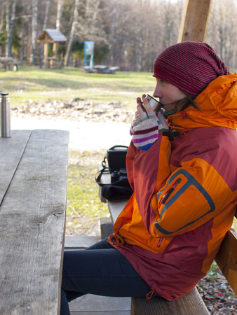 thermos: Girl sitting at a wooden table and drinking from a thermos.