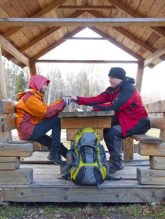 thermos: Man and woman sitting in a wooden gazebo in the woods and drink from a thermos hot drink.
