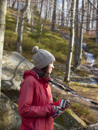 warm drink: A young girl stands in the forest among the rocks with a warm drink in a mug. Stock Photo