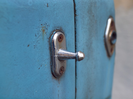 rusty car: Old latch on blue and rusty car.