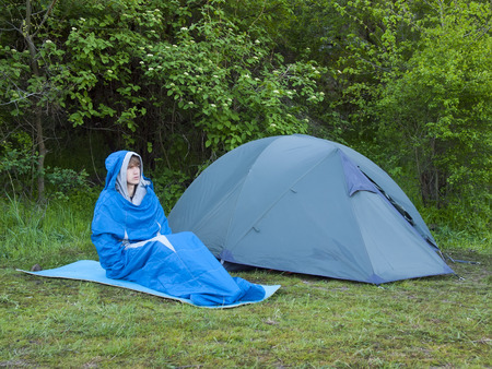 sleeping bag: The man is resting in a sleeping bag on the background of tents and green forests. Stock Photo
