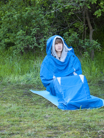 sleeping bag: The man is resting in a sleeping bag on the background of green forest.