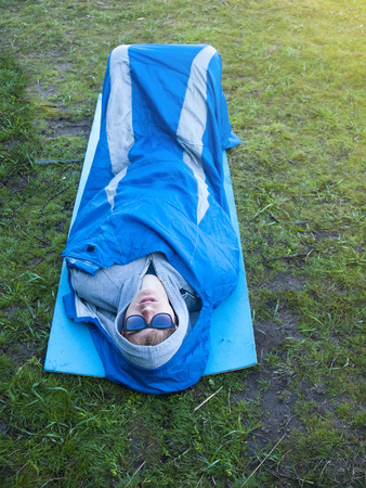 sleeping bag: The man is resting in a sleeping bag on a background of green grass.