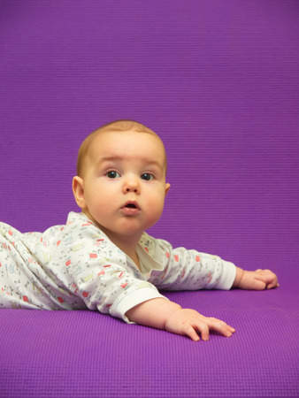 Infant on a purple background. Baby on a purple background. Archivio Fotografico