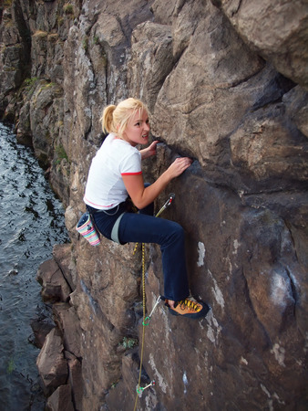 A young climber climbs on the vertical wall.