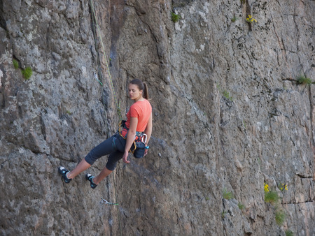 A young girl engaged in rock climbing at high rocks. Archivio Fotografico