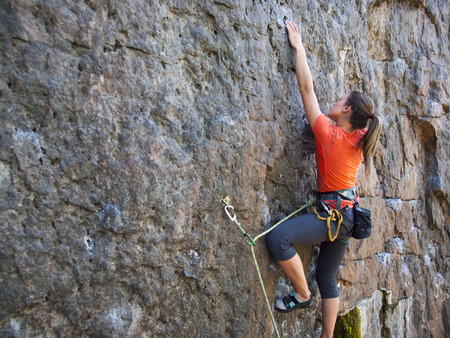 A young woman with a rope engaged in the sports of rock climbing on the rock. Imagens