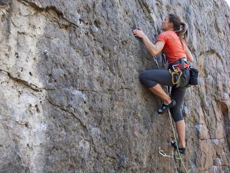 klimmer: Een jonge vrouw met een touw bezig met de sport van rotsklimmen op de rots.