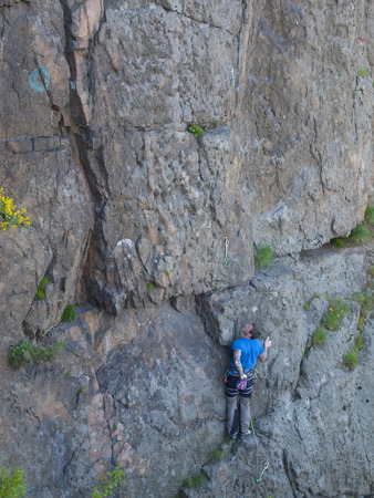 The man with the tattoos is engaged in rock climbing and climbs on the rock. photo