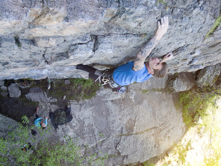 The man with the tattoos is engaged in rock climbing and climbs on the rock.