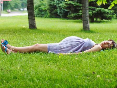The pregnant young woman lying on the grass. Stock Photo