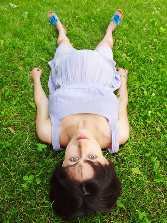 suitability: The pregnant young woman lying on the grass. Stock Photo