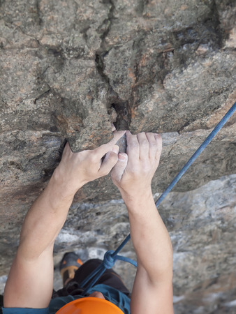 belaying: Hands of a climber who climbs on a difficult wall.