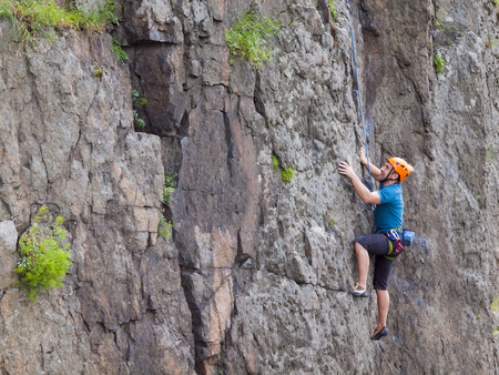 climbing: El escalador en naranja casco protector escaladas difíciles en la pared. Foto de archivo