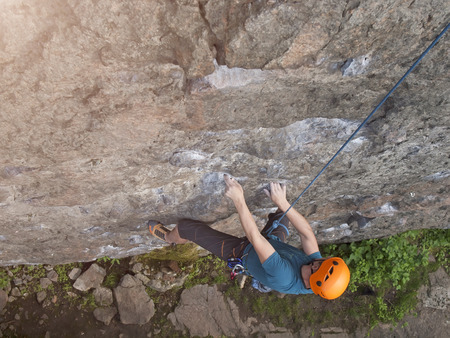 belaying: The climber in orange protective helmet difficult climbs on the wall. Stock Photo