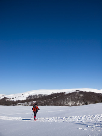 snowshoes: A man in snowshoes and a backpack resting in the mountains in the winter..
