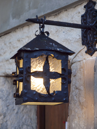 weighs: An old lamp that weighs on the facade of a historic building.