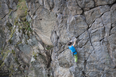 the rock: A young woman with a rope engaged in the sports of rock climbing on the rock. Stock Photo