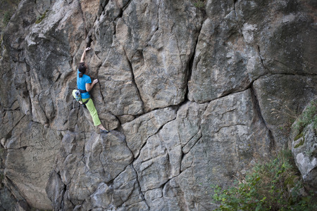 A young woman with a rope engaged in the sports of rock climbing on the rock. Archivio Fotografico