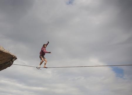balances: A young man balances on a highly tense slackline. Stock Photo