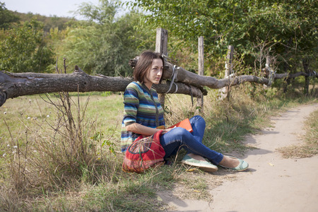 lonely person: Girl with backpack sitting near the road. Stock Photo