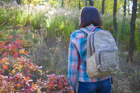bedspread: The girl with a backpack walks in the woods.
