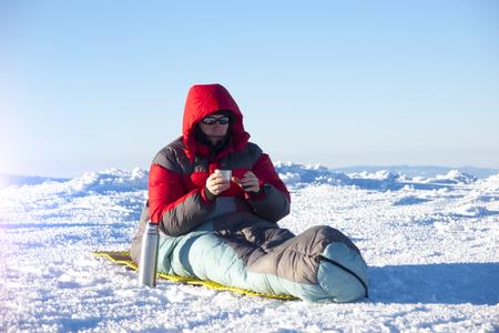 sleeping bag: A man sits in a sleeping bag and drinking tea