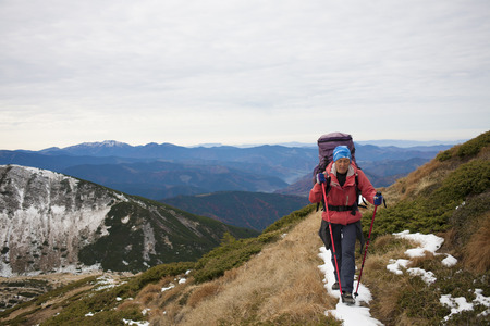 scarring: Girl with backpack is traveling in the mountains.
