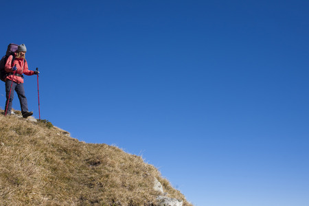 descends: The girl descends from the high mountains on the background of blue sky. Stock Photo
